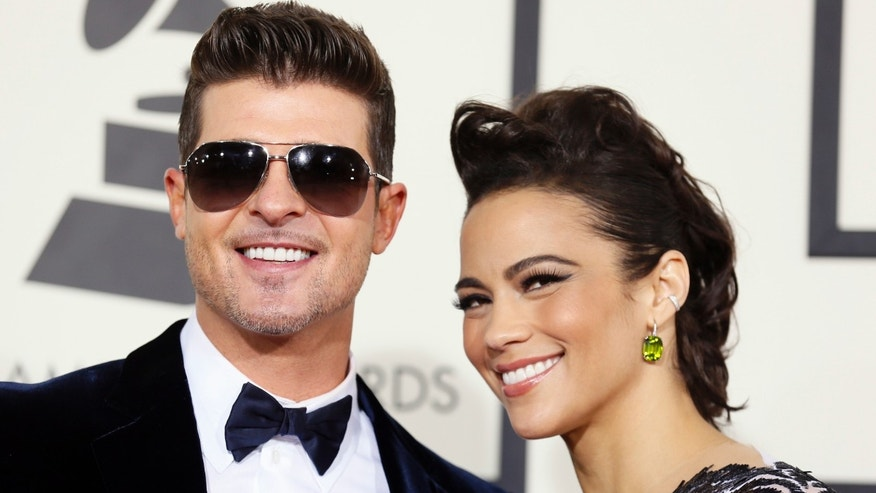 January 26, 2014. Singer Robin Thicke and wife, actress Paula Patton, arrive at the 56th annual Grammy Awards in Los Angeles, California.