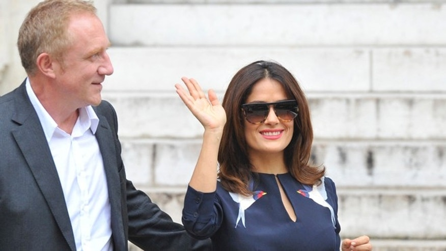 Mexican actress Salma Hayek waves as her husband Francois-Henri Pinault, CEO of luxury group Kering, looks on after Stella McCartney's Spring/Summer 2015 ready-to-wear fashion collection presented in Paris, France, Monday, Sept. 29, 2014. (AP Photo/Zacharie Scheurer)