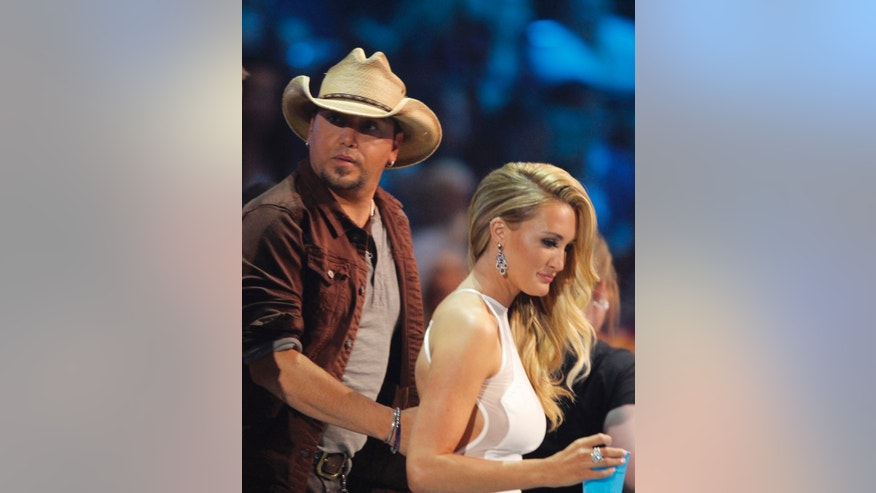 In this June 4, 2014 file photo, Jason Aldean, left, and his fiancee Brittany Kerr appear in the audience at the CMT Music Awards in Nashville, Tenn.