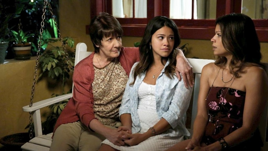 "In this image released by The CW, Ivonne Coll, from left, Gina Rodriguez and Andrea Navedo appear in a scene from ""Jane The Virgin,"" premiering Monday, Oct. 13, 2014. (AP Photo/The CW, Tyler Golden)"