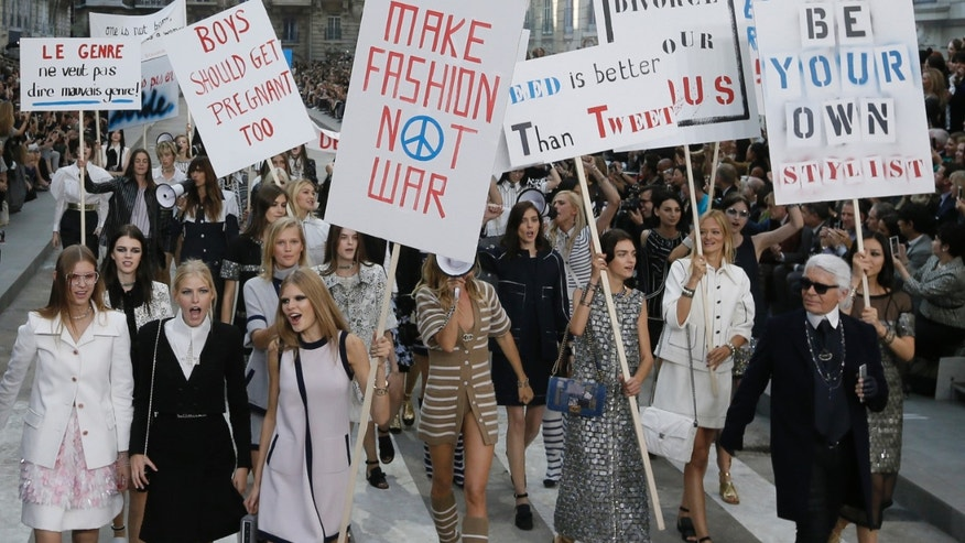 German designer Karl Lagerfeld (R) appears with models who stage a demonstration at the end of his Spring/Summer 2015 women's ready-to-wear collection for French fashion house Chanel during Paris Fashion Week September 30, 2014. Karl Lagerfeld created an immense Boulevard Chanel for his fashion show on Tuesday, even staging a street demonstration by fashionably dressed models for Spring/Summer 2015.     REUTERS/Gonzalo Fuentes (FRANCE - Tags: FASHION) - RTR48BXL