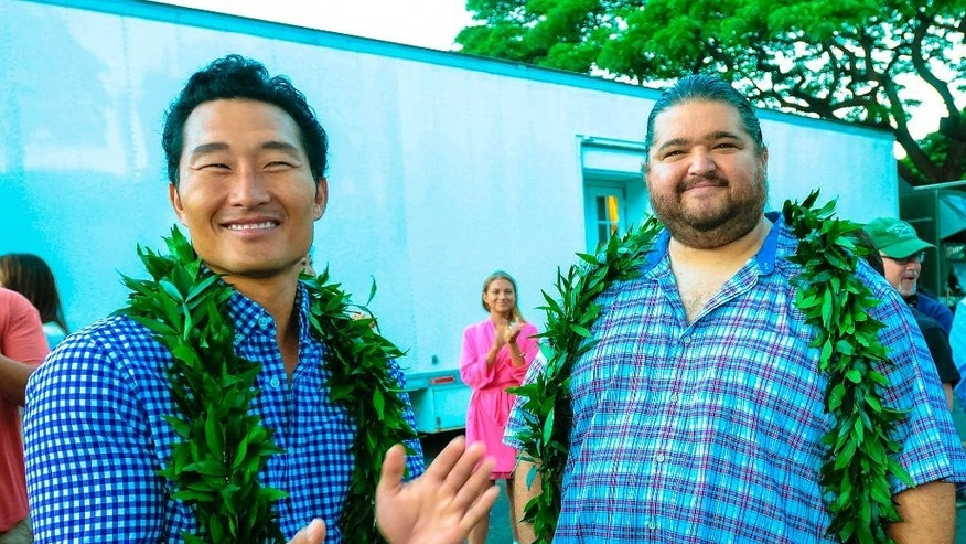 "This Tuesday, July 8, 2014 photo provided by CBS shows Daniel Dae Kim, left, and Jorge Garcia, as ""Hawaii Five-O"" kicked-off production on season 5 in Honolulu with a traditional Hawaiian blessing in honor of its host Hawaiian culture while on location in Waikiki. The former ""Lost"" star Garcia is back in Hawaii and liking it with his increased role on ""Hawaii Five-O."" (AP Photo/CBS, Norman Shapiro)"