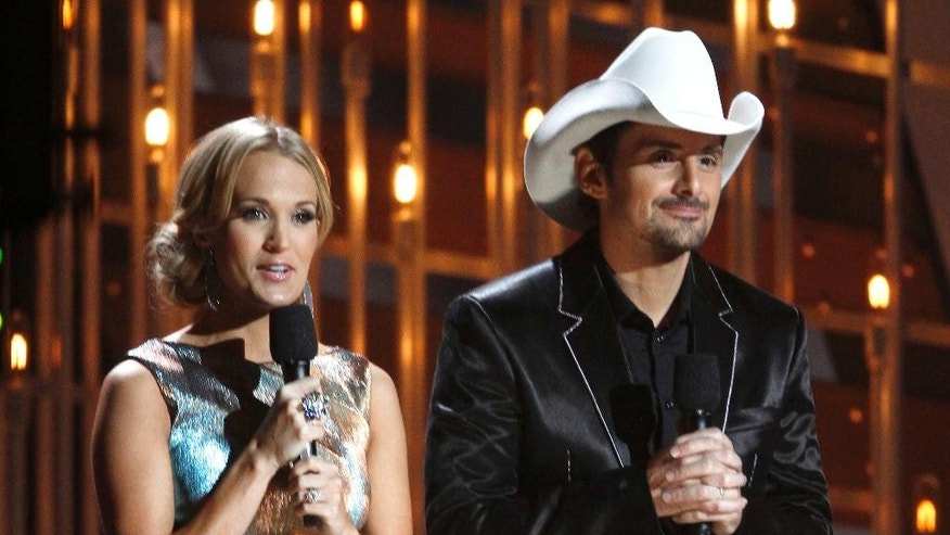FILE - In this Nov. 6, 2013 file photo, co-hosts Carrie Underwood, left, and Brad Paisley appear at the 47th annual CMA Awards at Bridgestone Arena in Nashville, Tenn. The pair will host the annual awards show on Wednesday, Nov. 5, 2014. (Photo by Wade Payne/Invision/AP)