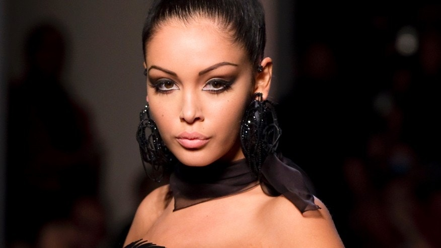 French reality TV star Nabilla Benattia presents a creation by French designer Jean Paul Gaultier as part of his Haute Couture Fall Winter 2013/2014 fashion show in Paris July 3, 2013.
