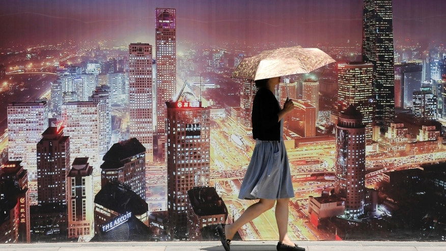A woman walks past a wall bearing an image of Beijing's skyscrapers outside a construction site for a new residential complex in Beijing June 18, 2013. China's house prices rose at the fastest pace this year in May from a year earlier, though the pace of monthly gains slowed, highlighting the dilemma facing the central bank as it balances the need to support the economy against holding down housing inflation. REUTERS/Kim Kyung-Hoon (CHINA - Tags: BUSINESS REAL ESTATE) - RTX10RNB