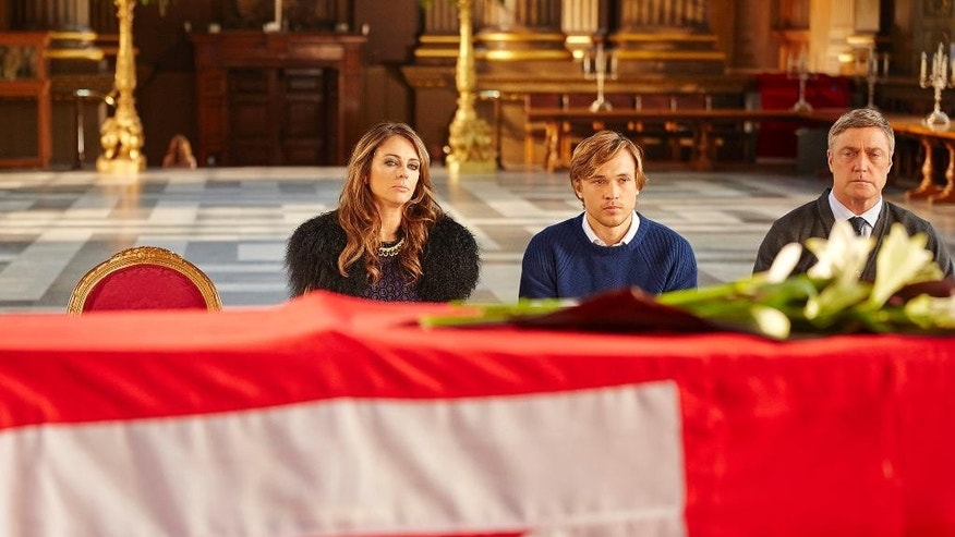 "This image released by E! shows Elizabeth Hurley as Queen Helena, left, William Moseley as Prince Liam, and Vincent Regan as King Simon, right, in a scene from ""The Royals,"" a scripted series about the lives of a fictional royal family set in modern day London. The series premieres in March 2015. (AP Photo/E!, Paul Blundell)"