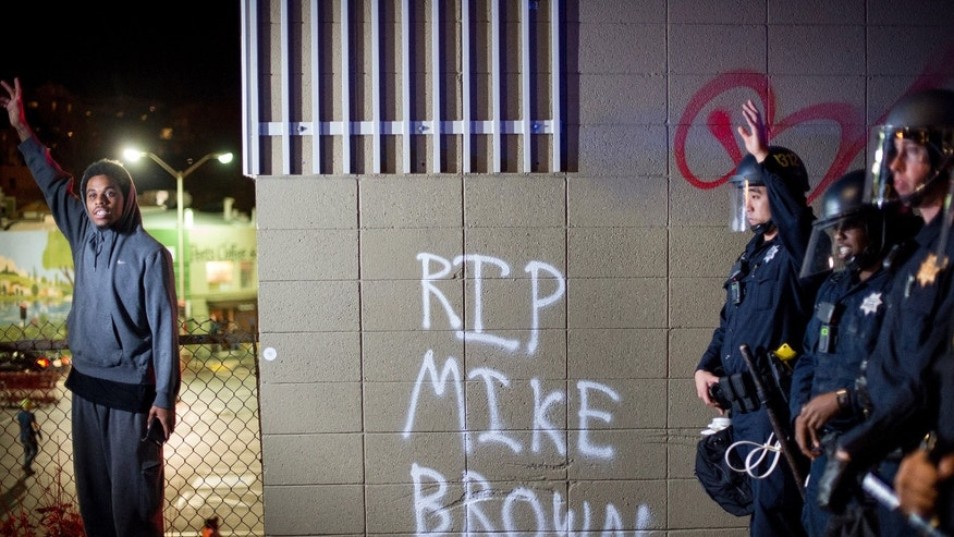 A protester near a wall with a graffiti and police officers in Oakland, Calif., on Monday, Nov. 24, 2014.
