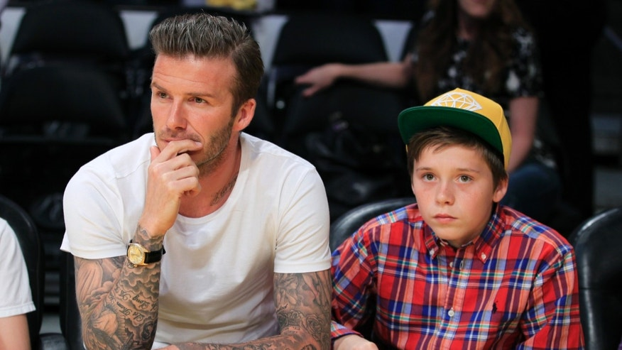 March 4, 2012. Soccer star David Beckham (L) and his son Brooklyn watch the Los Angeles Lakers play the Miami Heat in their NBA basketball game in Los Angeles, California.
