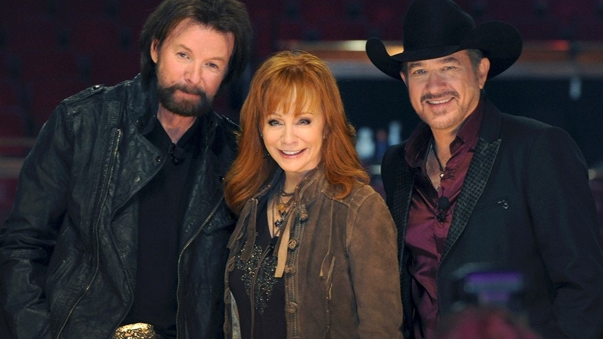 In this photo provided by the Las Vegas News Bureau, country music stars Reba McEntire, center, poses with Ronnie Dunn, left, and Kix Brooks, of the duo Brooks & Dunn, Wednesday, Dec. 3, 2014, in the Colosseum at Caesars Palace in Las Vegas.