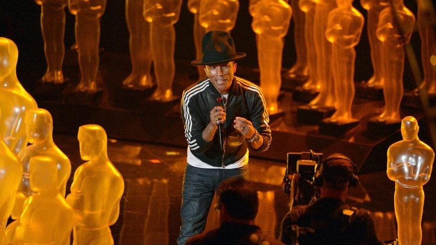 "FILE - In this March 2, 2014 file photo, Pharrell Williams performs ""Happy"" during the Oscars at the Dolby Theatre in Los Angeles. Spotify announced its top streaming artists, albums and songs of 2014 on Wednesday, Dec. 3, 2014. Pharrell's ubiquitous ""Happy"" was the most streamed song of the year globally.  (Photo by John Shearer/Invision/AP, File)"