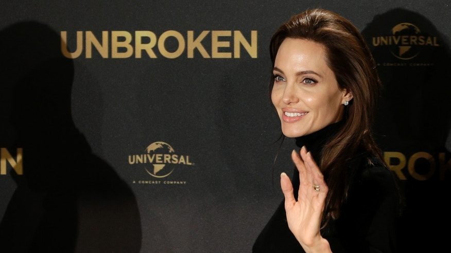 "November 27, 2014. Angelina Jolie waves as she leaves after a photo call for the movie ""Unbroken"" in Berlin, Germany."