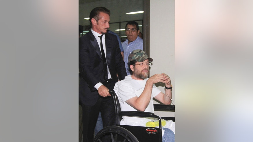 FILE - In this Dec. 11, 2012 file photo, actor Sean Penn pushes U.S. businessman Jacob Ostreicher in a wheelchair, during a recess at Ostreicher's hearing in Santa Cruz, Bolivia. In the year since Ostreicher was spirited out of Bolivia, the 55-year-old has struggled to rebuild a life upended by corrupt officials who tried to extort him and imprisoned him without charge. Ostreicher's ordeal began with an attempt to salvage ill-fated investment in Bolivian rice farms, devolved into a Third World prison nightmare and climaxed with an escape engineered by actor Sean Penn. (AP Photo, File)