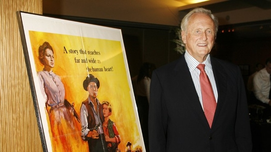 "June 15, 2006. Producer Samuel Goldwyn Jr. stands next to a poster of his film ""The Proud Rebel"" as he arrives for ""An Academy Tribute to Olivia de Havilland"" at the Academy of Motion Picture Arts & Sciences in Beverly Hills."