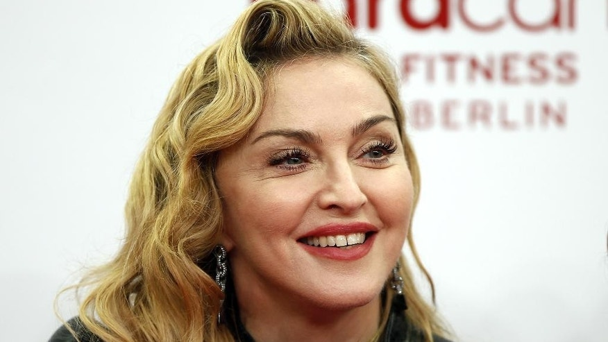 "FILE - In this Thursday, Oct. 17, 2013, file photo, U.S. pop star Madonna smiles during her visit at the ""Hard Candy Fitness"" center in Berlin. Madonna, AC/DC and Ariana Grande are among the first performers set to take the stage at the Grammy Awards on Feb. 8, 2015, in Los Angeles. (AP Photo/Michael Sohn, File)"