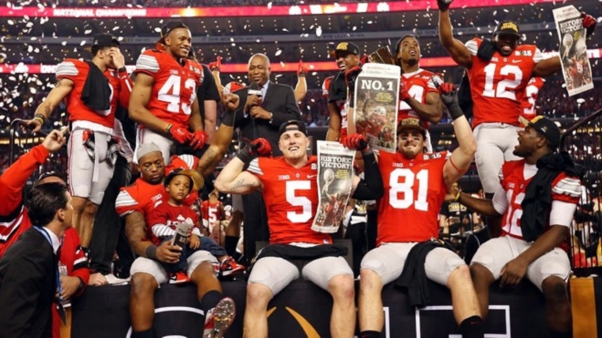 Jan 12, 2015; Arlington, TX, USA; Ohio State Buckeyes players celebrate on the podium after the 2015 CFP National Championship Game against the Oregon Ducks at AT&T Stadium. Mandatory Credit: Matthew Emmons-USA TODAY Sports - RTR4L72A