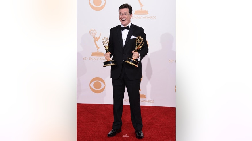 "FILE - In this Sept. 22, 2013, file photo, Stephen Colbert, winner of the best writing for a variety series award and best variety series award for ""The Colbert Report,"" poses backstage at the 65th Primetime Emmy Awards at Nokia Theatre in Los Angeles. Larry Wilmore's new Comedy Central show, ""The Nightly Show with Larry Wilmore,"" premieres on Monday, Jan. 19, 2015. Wilmore will replace Colbert in the time slot following ""The Daily Show,"" with Jon Stewart. (Photo by Dan Steinberg/Invision/AP, File)"
