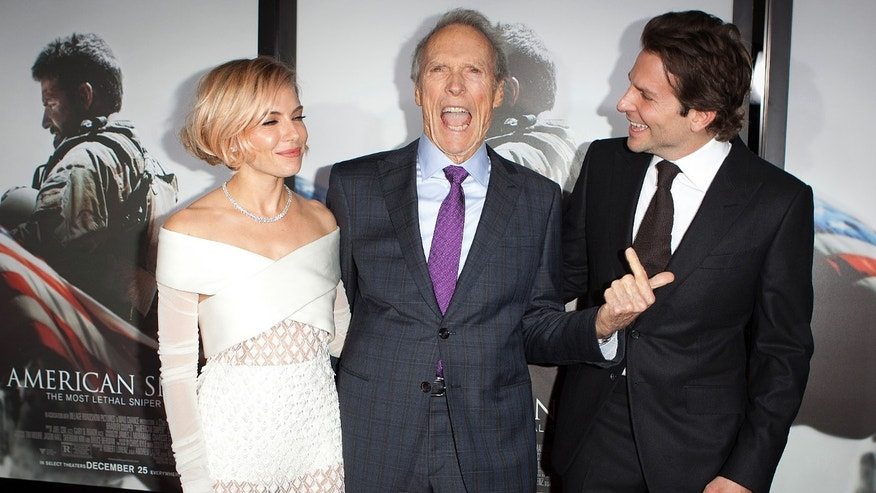 """December 15, 2014. Actress Sienna Miller (L), director Clint Eastwood and actor Bradley Cooper ( R) arrive for the premiere of the film """"American Sniper"""" in New York."""