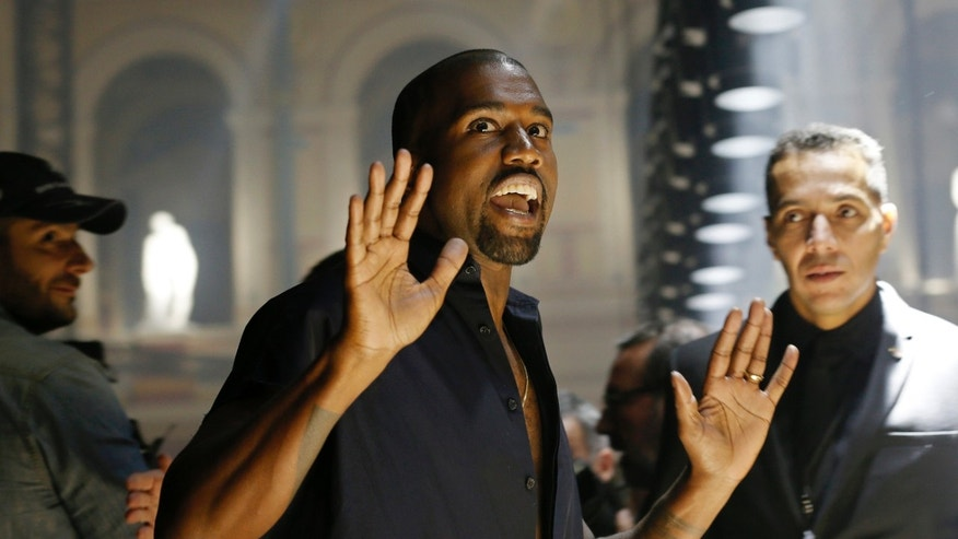 September 25, 2014. Rapper Kanye West reacts as he arrives to attend the Israeli-American designer Alber Elbaz Spring/Summer 2015 women's ready-to-wear collection for fashion house Lanvin during Paris Fashion Week.