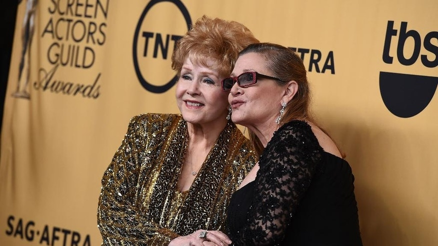Debbie Reynolds, winner of the Screen Actors Guild lifetime award, left, and Carrie Fisher pose in the press room at the 21st annual Screen Actors Guild Awards at the Shrine Auditorium on Sunday, Jan. 25, 2015, in Los Angeles. (Photo by Jordan Strauss/Invision/AP)