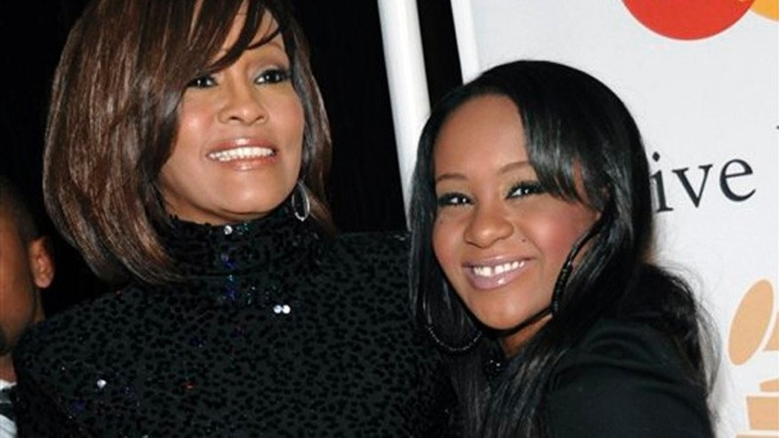 FILE - Feb. 12, 2011: Singer Whitney Houston, left, and daughter Bobbi Kristina Brown arrive at an event in Beverly Hills, Calif.