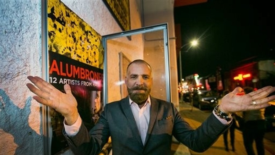 "Cuban producer Fermin Rojas poses with the poster of his film, ""Alumbrones"" in Los Angeles."