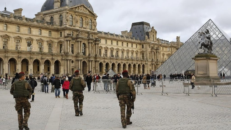 FILE - In this  a Jan.10 2015 file photo, of French soldiers as theypatrol near the Louvre Museum in Paris. Fearing that actors could be mistaken for police and chase scenes confused for the real thing  Paris is sharply restricting filming of action movies in the city that been the stage for some of film's most memorable high-octane sequences. Filming outside scenes with police, army or security services was quietly banned after the attacks in the French capital that left 20 dead, including three gunmen. (AP Photo/Laurent Cipriani, File)