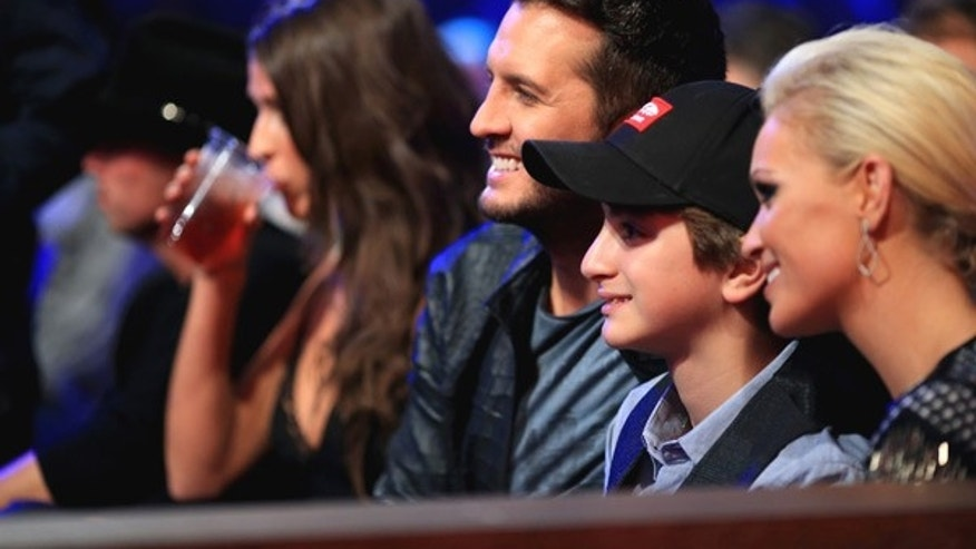 From left to right: Luke Bryan his nephew Til and his wife Caroline at the American Country Countdown Awards, Dec 15. in Nashville.