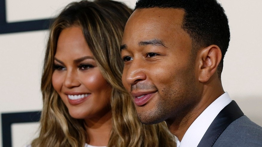 Singer John Legend arrives with wife Chrissy Teigen at the 57th annual Grammy Awards in Los Angeles, California February 8, 2015.