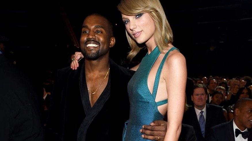 Kanye West and Taylor Swift pose for a photo together at the 2015 Grammy Awards.