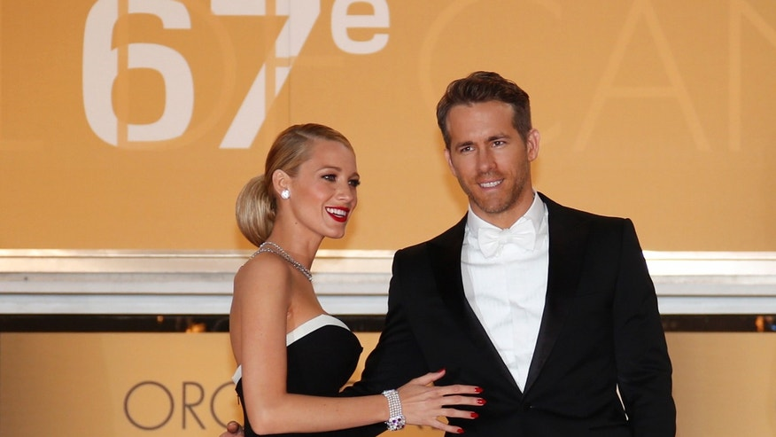 "Cast member Ryan Reynolds (R) and his wife actress Blake Lively pose on the red carpet as they arrive for the screening of the film ""Captives"" (The Captive) in competition at the 67th Cannes Film Festival in Cannes May 16, 2014.                    REUTERS/Benoit Tessier (FRANCE  - Tags: ENTERTAINMENT)   - RTR3PJKX"