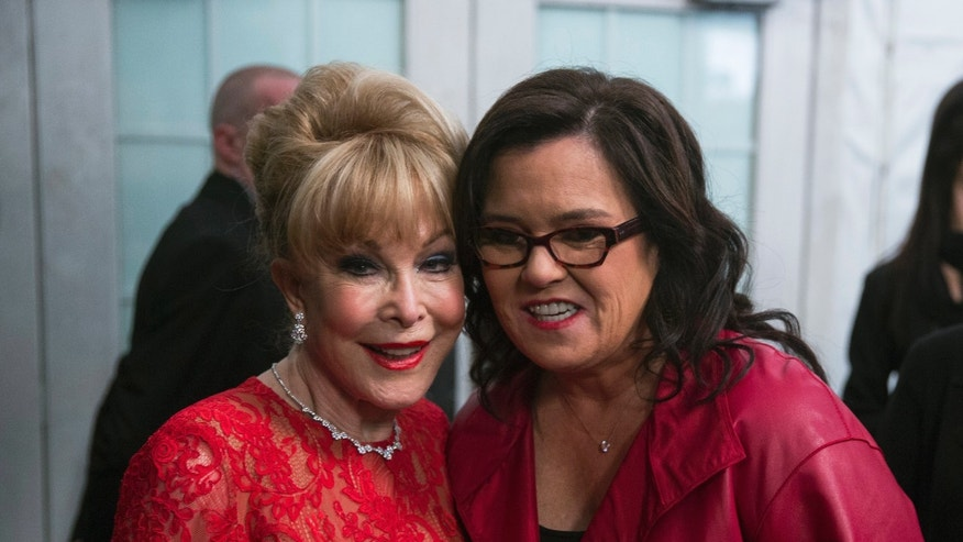 Actresses Rosie O'Donnell (R) and Barbara Eden smile for a photograph before presenting a creation from the Go Red for Women Red Dress collection during New York Fashion Week February 12, 2015. REUTERS/Lucas Jackson (UNITED STATES - Tags: FASHION SOCIETY ENTERTAINMENT) - RTR4PEDA