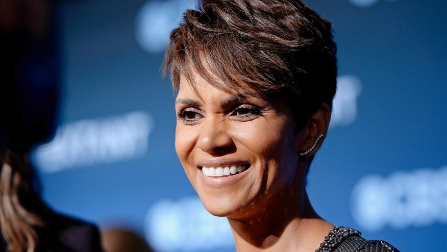"June 16, 2014. Cast member Halle Berry of the CBS science fiction television series ""Extant,"" smiles during an interview at the premiere of the series at the Samuel Oschin Space Shuttle Endeavour Display Pavilion in Los Angeles, California."
