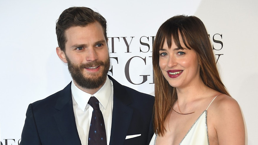"Feb 12, 2015. Dakota Johnson, right, and Jamie Dornan pose for photographers at the UK Premiere of  ""Fifty Shades of Grey"" in London."
