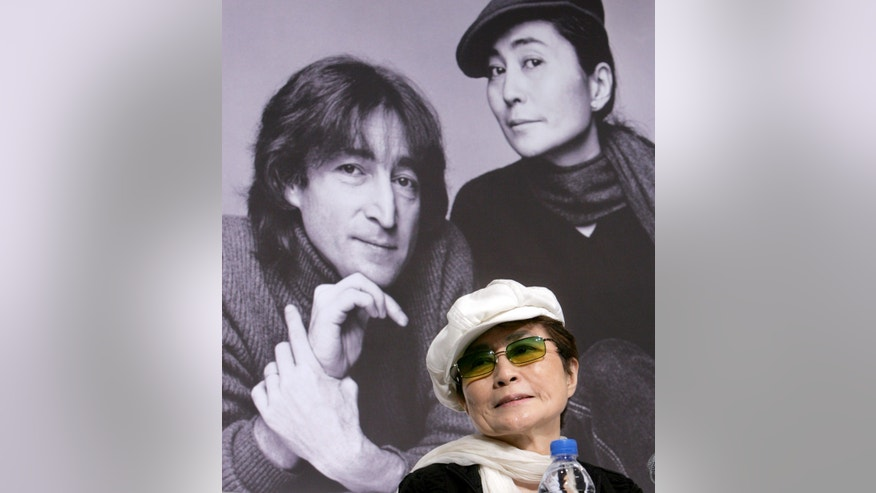 October 4, 2005. Yoko Ono, the wife of the late singer John Lennon, listens to reporters questions in front of a portrait of Lennon and herself at a news conference in Tokyo.