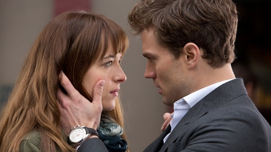 Dakota Johnson, left, and Jamie Dornan appear in a scene from the film, 'Fifty Shades of Grey.'