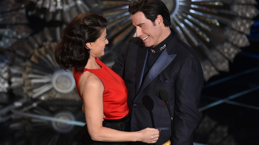 Idina Menzel, left and John Travolta present the award for best original song at the Oscars on Sunday, Feb. 22, 2015, at the Dolby Theatre in Los Angeles.
