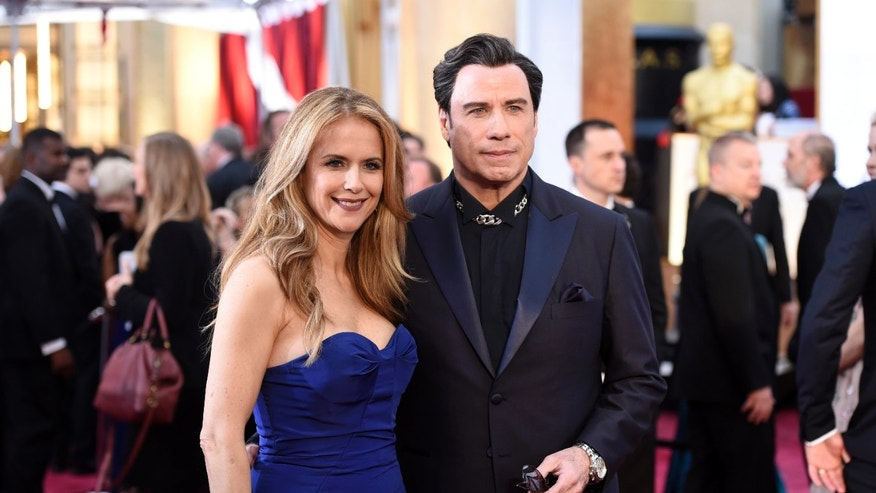 Kelly Preston, left, and John Travolta arrive at the Oscars on Sunday, Feb. 22, 2015, at the Dolby Theatre in Los Angeles. (Photo by Chris Pizzello/Invision/AP)
