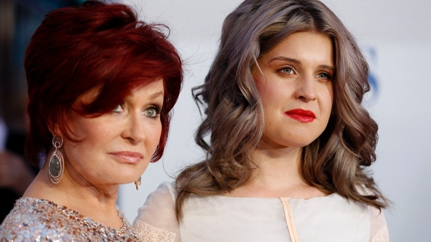 Television host Sharon Osbourne (L) and her daughter Kelly Osbourne pose as they arrive at the 2012 People's Choice Awards in Los Angeles January 11, 2012.