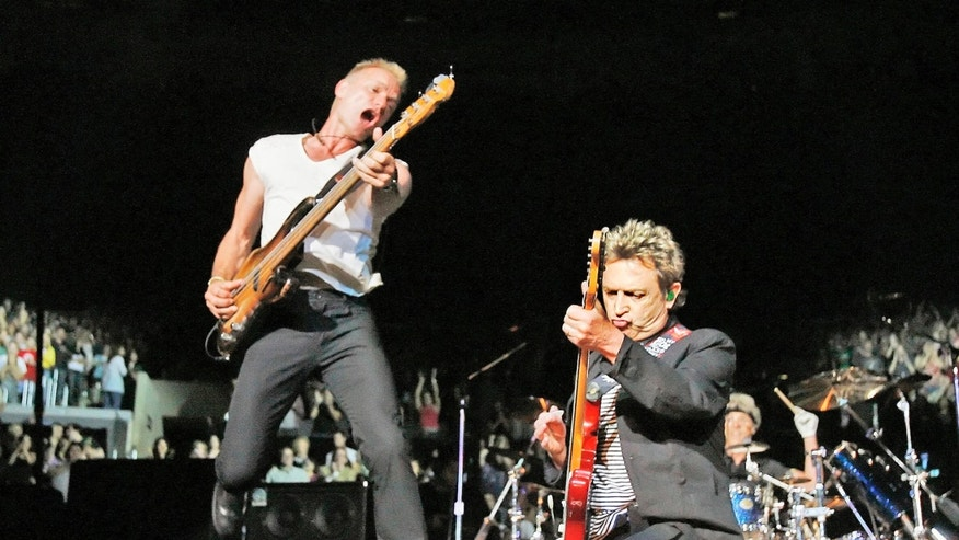 """Andy Summers, right, guitarist, for the rock band  The Police, performs as Sting, bassist and lead singer of the rock band, leaps in the air upon as they complete the  song """"Synchronisity"""" with drummer Stewart Copeland, at the Staples Center in Los Angeles Wednesday, June 20, 2007. The band last played in Los Angeles on Sept. 6, 1983, at Hollywood park. This was the first of three shows in Southern California. (AP Photo/Kevork Djansezian)"""