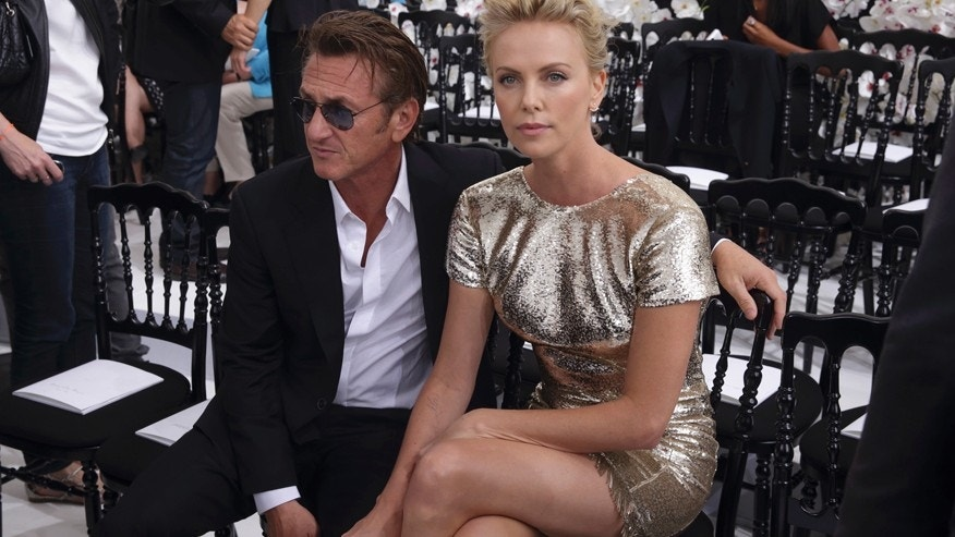 Actors Sean Penn (L) and Charlize Theron pose prior to the French fashion house Christian Dior Haute Couture Fall/Winter 2014-2015 fashion show by Belgian designer Raf Simons in Paris July 7, 2014.
