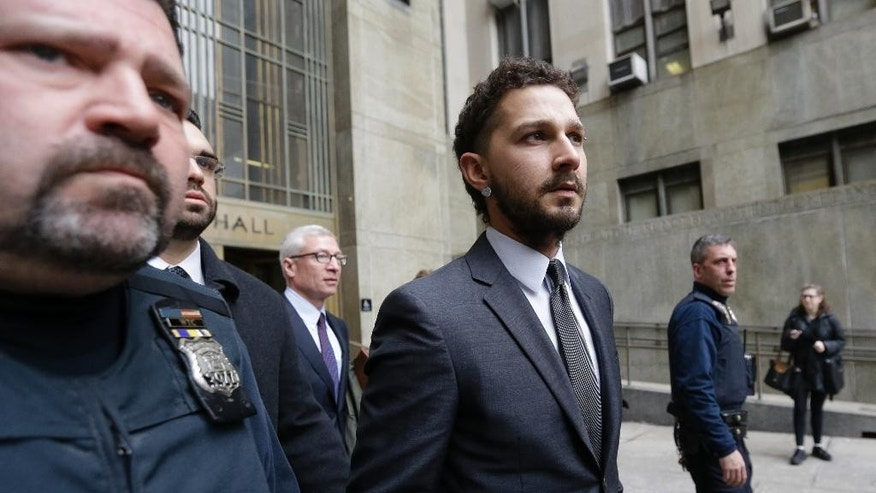 Actor Shia LaBeouf, center, is escorted by court officers as he leaves Manhattan Criminal court, Friday, March 20, 2015, in New York.  (AP Photo/Mary Altaffer)