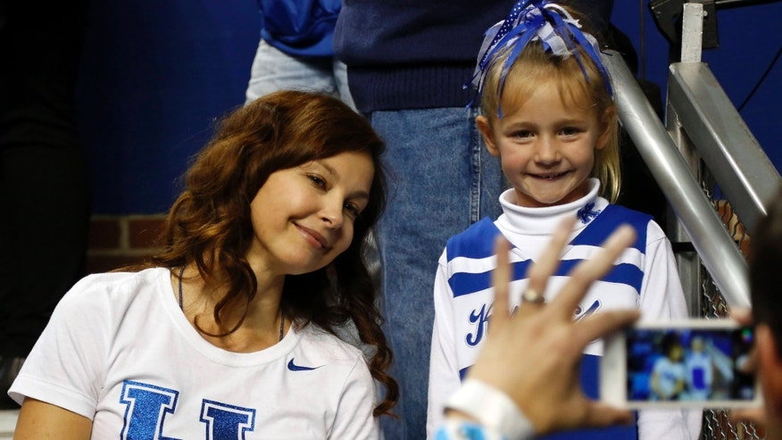 March 7, 2015: Actress Ashley Judd, left, poses with a young fan after an NCAA college basketball game between Florida and Kentucky.