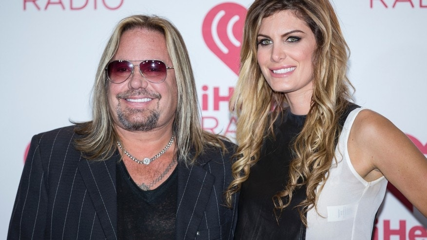 In this Sept. 19, 2014 file photo, Vince Neil and girlfriend Rain Andreani arrive at the iHeart Radio Music Festival, at The MGM Grand Garden Arena in Las Vegas.