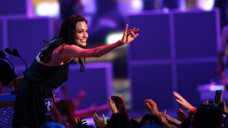 March 28, 2015. Angelina Jolie waves as she accepts the Best Villain Award at the 2015 Kids' Choice Awards in Los Angeles, California.