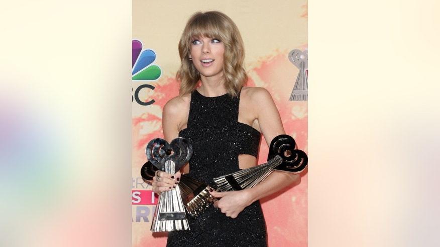 "Taylor Swift poses in the press room with the awards for best lyrics for ""Blank Space"", song of the year for ""Shake It Off"" and artist of the year at the iHeartRadio Music Awards at The Shrine Auditorium on Sunday, March 29, 2015, in Los Angeles. (Photo by John Salangsang/Invision/AP)"