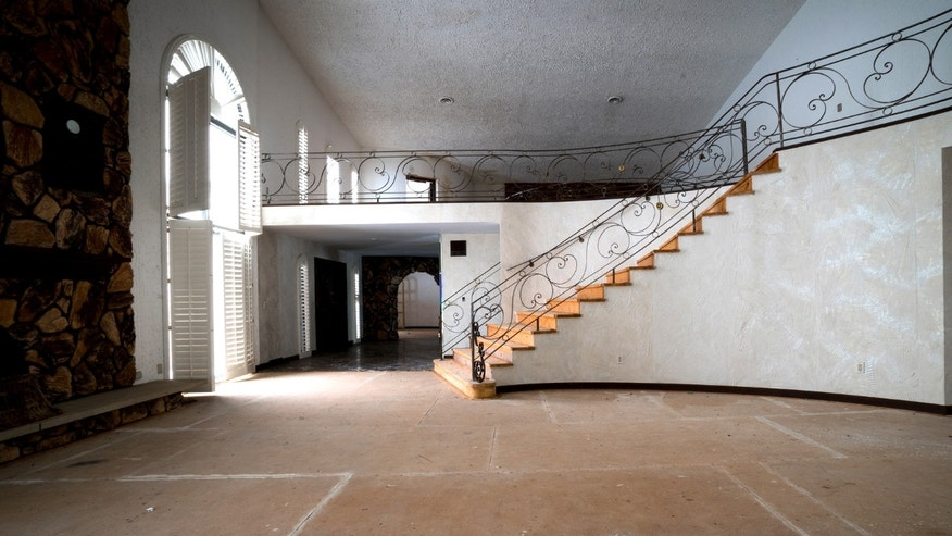 One of the Grand staircases with an open fire at the bottom at Mike Tyson's abandoned mansion.