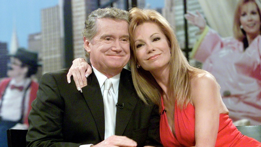 """Talk show host Kathie Lee Gifford (R) hugs her co-host Regis Philbin during Gifford's final appearance on their popular morning show """"Live With Regis and Kathie Lee"""" July 28, 2000. Gifford is leaving the program after 15 years co-hosting along-side Philbin who will remain with the program under it's new name, """"Live with Regis"""".MS - RTR6R78"""
