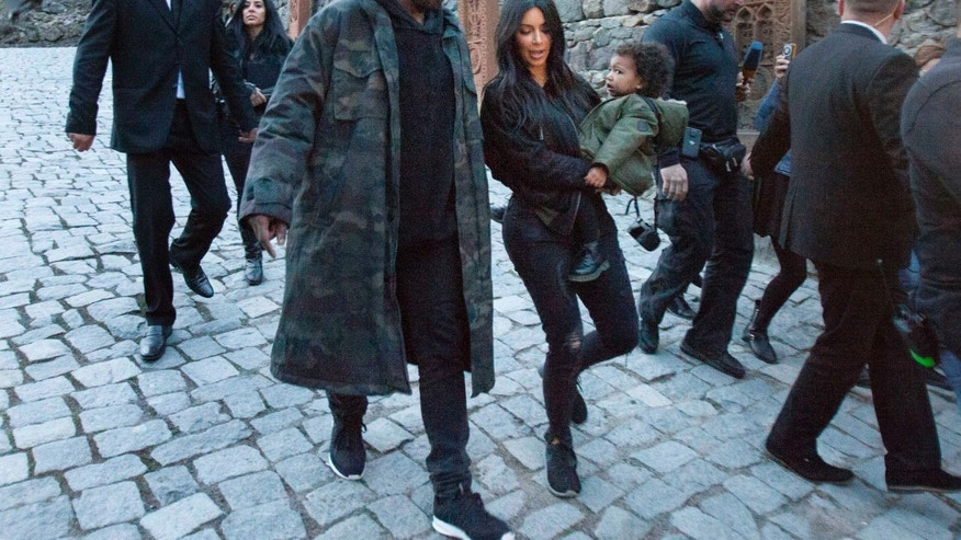 April 9, 2015. Kim Kardashian, center, carriers daughter North as she walks alongside her husband Kanye West during a visit to the Geghard Monastery near Goght in Armenia.