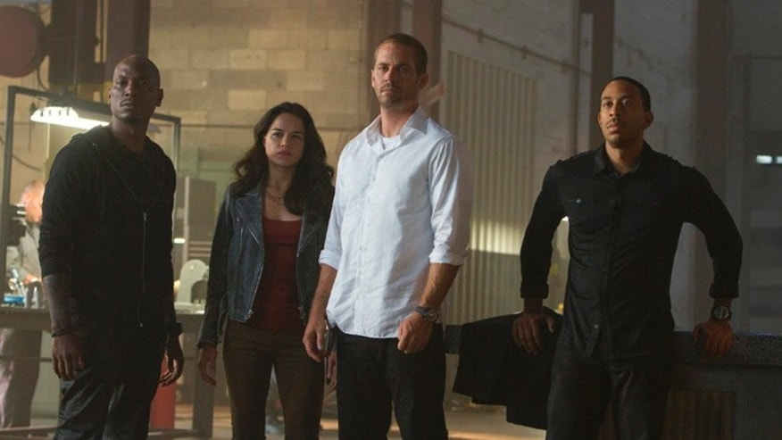 "Tyrese Gibson as Roman, Michelle Rodriguez as Letty, Paul Walker as Brian, and Chris Ludacris as Tej, in a scene from ""Furious 7."""