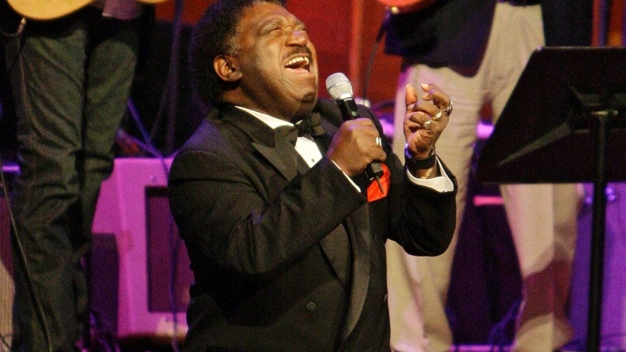 "In this Oct. 28, 2008 file photo, Percy Sledge kneels as he performs ""When a Man Loves a Woman"" along with the Muscle Shoals Rhythm Section at the Musicians Hall of Fame awards show in Nashville, Tenn."